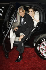Senior African couple getting out of limousine