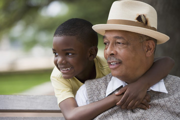 African boy hugging grandfather outdoors