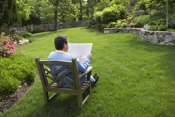 Hispanic man reading in backyard