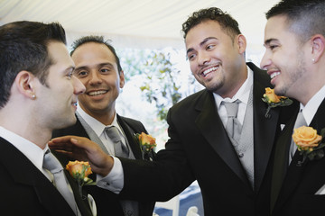Multi-ethnic men wearing tuxedos