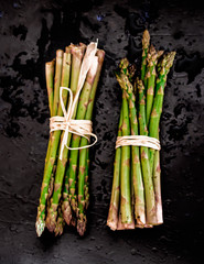 two bunch of asparagus on black background