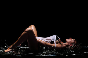 Young sexy nude woman posed wet. Water studio photo.