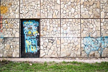 Vandalized Door and Stone Wall