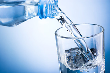 Close-up pouring water from bottle into glass on a blue backgrou
