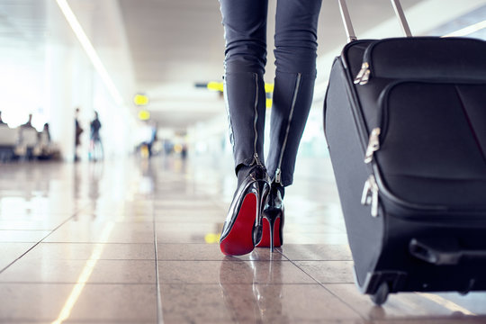 Woman walking in airport with hand luggage suitcase