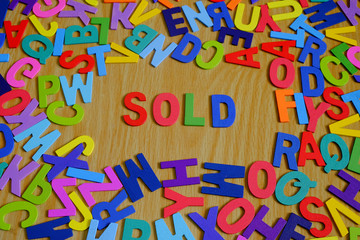 SOLD Colorful conceptual words on alphabet letters with Background texture of wood.