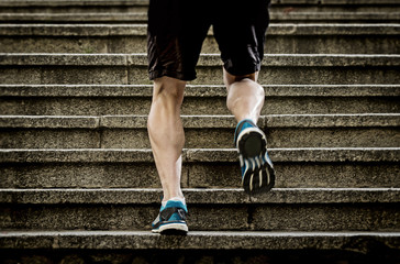 fit strong legs of sport man running steps in  urban training