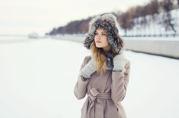 Portrait of a beautiful woman dressed a coat and fur hat in the
