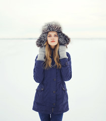 Portrait of a beautiful woman in a fur hat, winter field