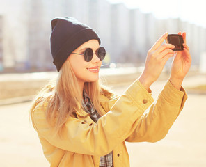 Portrait pretty blonde makes selfie-portrait on the smartphone,