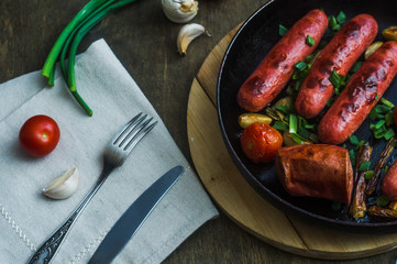 grilled sausages with vegetables in a frying pan
