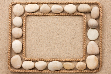 Beautiful frame with rope and white stones on sand