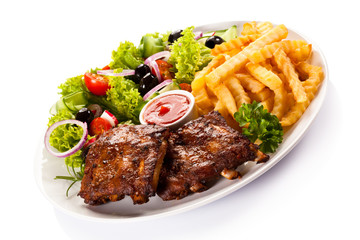 Grilled ribs, French fries and vegetables on white background