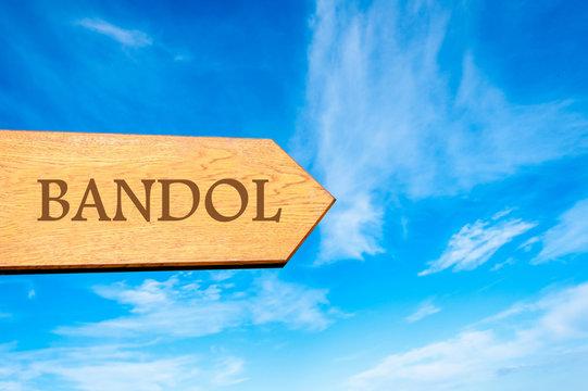 Wooden arrow sign pointing destination BANDOL, FRANCE