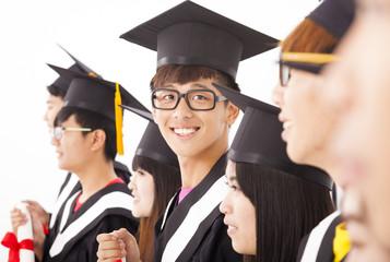 asian male college graduate at graduation with classmates