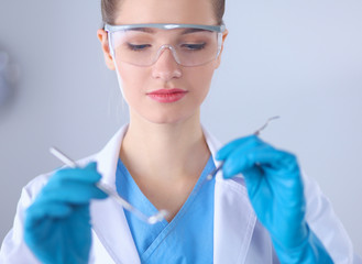 Attractive female dentist with tools , standing on gay