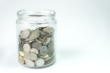 Isolated coins in jar - financial concept.