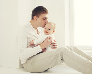 Young father kissing baby at home in white room near window