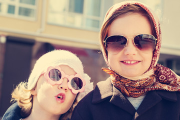 Little girls (sisters) in a headscarf and sunglasses.