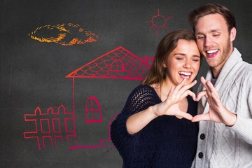 Composite image of happy couple forming heart with hands