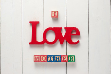 Happy mother's day concept - I love mother sign over white wood background