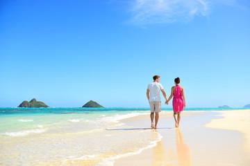 Beach couple holding hands walking on Hawaii