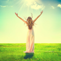 Beautiful woman outdoor raising hands in sunlight rays
