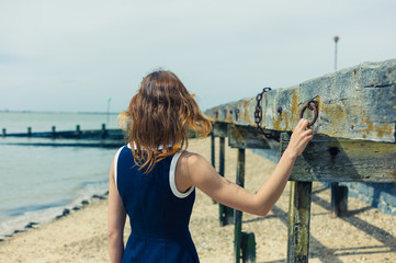 Young woman standing on beach with old wooden structure