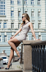 Young beautiful woman in beige short dress posing outdoors in su