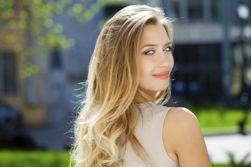 Portrait close up of young beautiful blonde woman, on background
