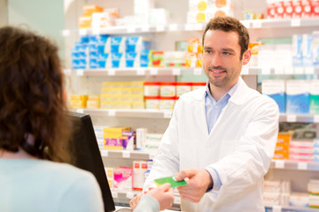 Attractive pharmacist taking healt insurance card
