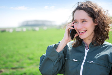 Young attractive farmer in a field using mobile phone