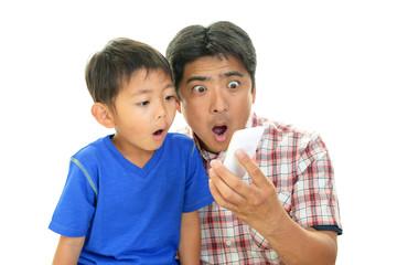 スマートフォンを持つ親子