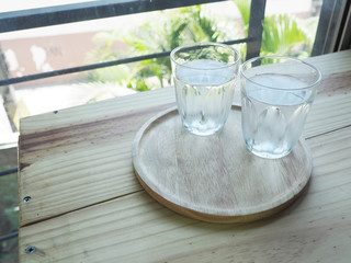 Glass of water on wood table bar background.