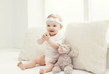 Cute baby playing at home in white room near window