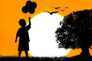 Silhouette of the boy standing and holding bubble