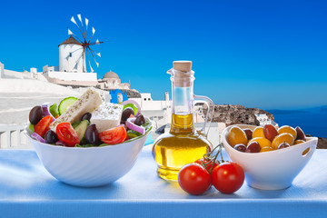 Greek salad against windmill in Santorini island, Greece