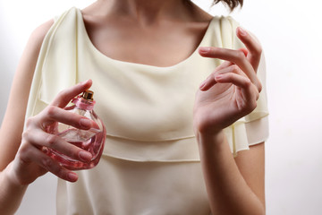 Woman spraying perfume on her wrist, closeup