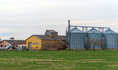 Factory and industrial silos near green field.