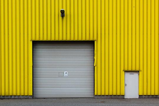 gelbe Wellblechfassade mit Tor und Tür