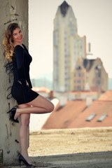 fashion woman posing in small black dress at cityscape
