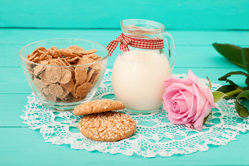 Breakfast with jug of milk and cookies on blue wooden background.Selective focus