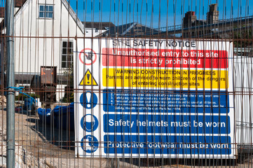 Warning signs at a construction site behind a fence
