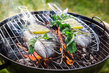 Photo sur Plexiglas Poisson Grilling tasty fish with herbs and lemon