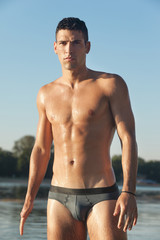 Muscular man in swim briefs getting out of water