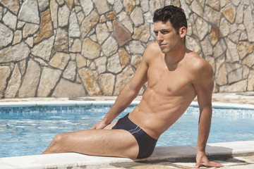 Handsome man in swim briefs by the pool