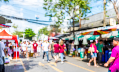 Blurred background : people shopping at market fair in sunny day