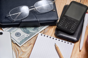 Workplace with notebook, phone, laptop, money, glasses.