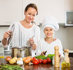 Smiling girl and mom at kitchen
