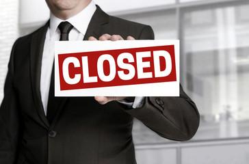Geschäftsmann hält closed schild entgegen